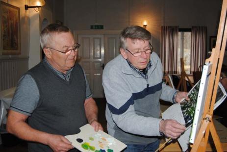 Tommy instruerar Lars Andersson inom måleriets ädla konst.