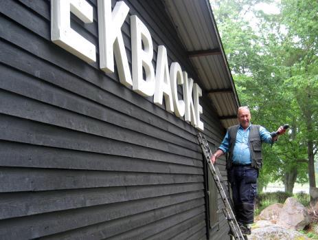 Stikkan sätter upp den fina skylten som han själv konstruerat och tillverkat.
