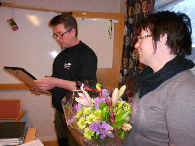 Urban läser motiveringen och Anki står beredd med blommorna.