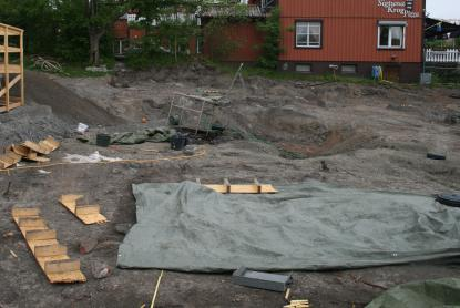 Utgrävningsplatsen delvis täckt av presenningar för att skydda mot sol och regn
