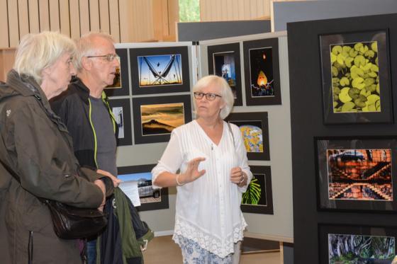 Karina Gustafson diskuterar sina bilder med ett par av besökarna.
