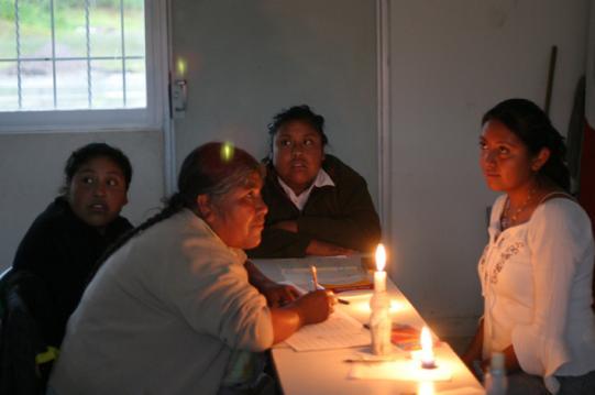 En kvinna med sina två döttrar i en undrvisningsgrupp. Man hade inte kunnat betala el-räkningen,så ett stearinljus fick duga som belysning.