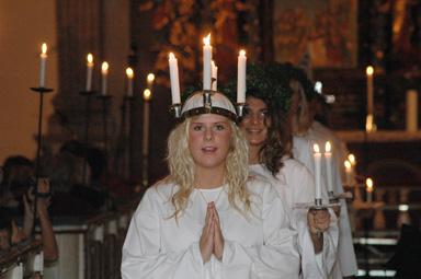 Lucia med tärnor tågar ut ur Bollebygds kyrka.
