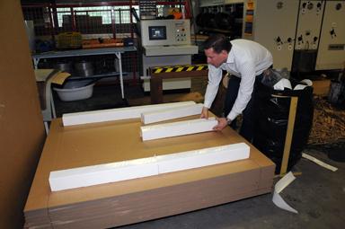Här bygger Dennis Artursson en pall av pappersemballage.