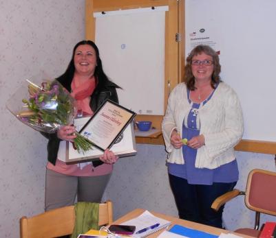 Årsmötets ordförande Anita Lindström överlämnar blommor och utmärkelse till Susanne Oldenborg.