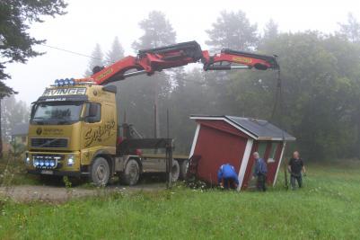 Här ska just stugan lyftas upp på Svinges bil.