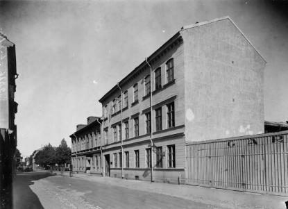 Bertil Nordholm bodde nära skolan i det bortre av husen på Norra Slottsgatan. Där infarten till Flanörs parkeringshus finns. I bakgrunden kan träden på Vasaskolans gård ses.