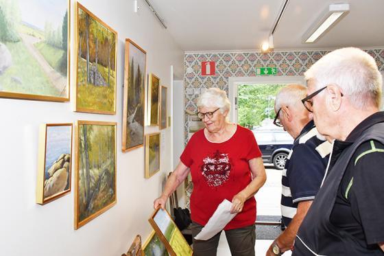 Dottern Barbro och hennes man Martti Mattinen hänger Ellen Johansson konst.<br />En av museets ansvariga, Agne Johansson servar med<br />hammare och spik.