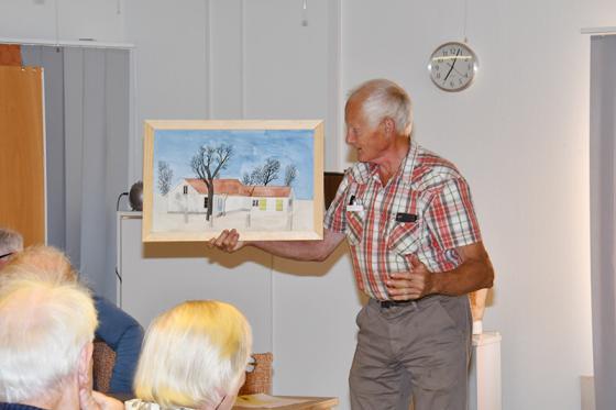 Leif Karlsson visar upp en målning föreställande Tingshuset. Leif Karlsson har själv målat tavlan.