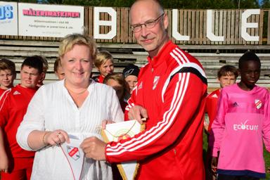 Sue Frisk, ordförande i Hestrafors IF och Niclas Reich, lagledare för Håbo FF:s P03 lag byter vimplar med varandra.