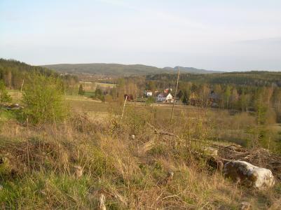 Här ser man delar av den ena gravhögen till vänster i bild och sen utsikten över byn.