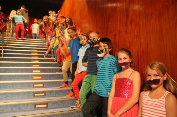 Barnen står vid trapporna och välkomnar alla.