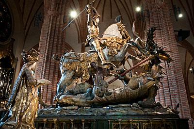 St Göran och draken. Allegorisk staty från 1400-talet. Riddaren symboliserar Sten Sture dä. som besegrar den hemska draken Danmark och försvarar kvinnan, Sverige.