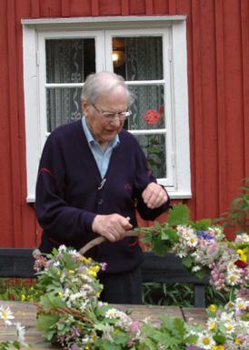 Holmer har i många år varit engagerade i Bollebygds Hembygdsförening. Därför har han också varit med och bundit blomsterkransar inför midsommarfirandet imånga år.