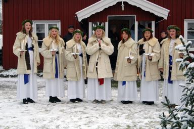 Lucia med tärnor framträdde farmför Åsenstugan i Bollebyds Hembygdspark.