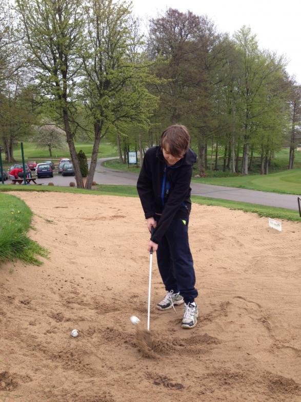 Sebastian tränar i bunkern och lyckas få upp både boll och sand.