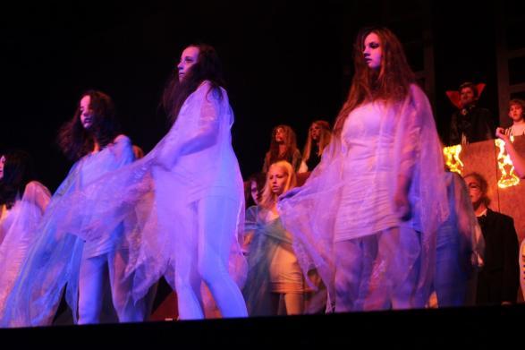 Spöklika dansare svävar över scenen som delvis består av en kyrkogård.