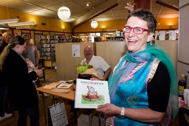 Gun Westin visar upp sin bok, Sagosoppan på biblioteket i Bollebygd.