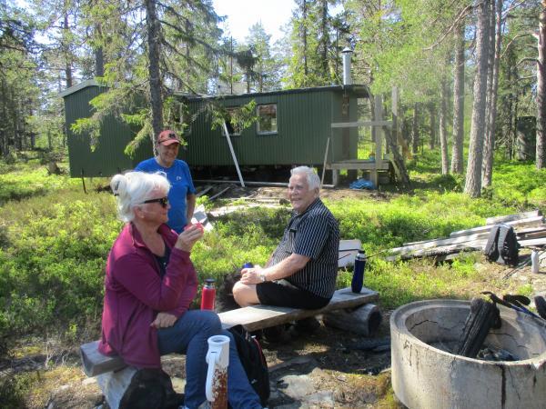 Anki, Tommy och Anders med jaktstugan i bakgrunden