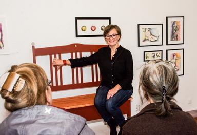 Lotta Claesson berättar för ett par besökare om soffan som hon visar på sin utställning.