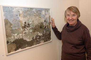 Här visar Berit Frändås upp en de fyra tavlorna som hon framställt med den egna tekniken. \