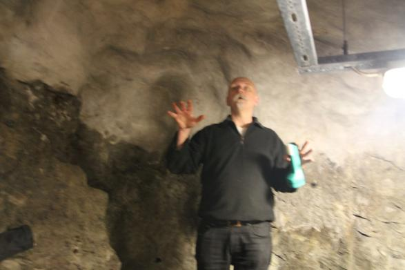 Mikael Helgesson står och berättar i en underjordiskt skyddsrum (guide)