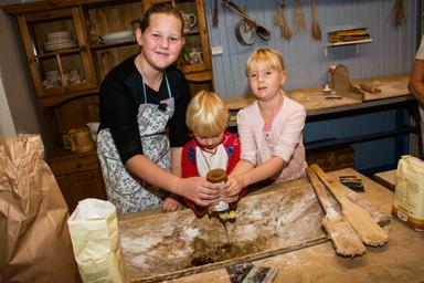 Emma Johansson och syskonen Sixten och Irma Lindeblom Hägg förser degen med rätt mängd sirap.