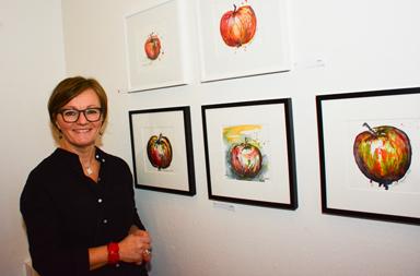 Lotta Claesson vid några av sin tavlor. Hon målar i akvarell och använder både den traditionella \