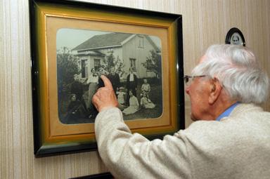 Holmer Alfredsson framför foto med föräldrar och syskon.