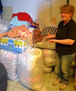 Eva Bylund visar på gåvor, som stickats och vävts av hjälpsamma medmänniskor i bygden.