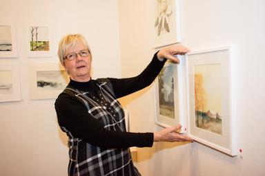 Här justerar Christina Björck en av sina akvareller.