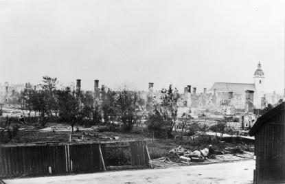 Här har fotografen av den första bilden svängt kameran åt höger, väster. I förgrunden rester efter staketet som omgav staden i bakgrunden Heliga Trefalighets kyrka.
