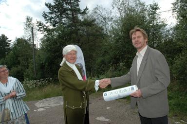 Kommunalrådet Peter Rosholm (s) tar emot budkavlen av Carl von Linné. I kanten övervakar Gunilla Adebahr, regional samordnare för Linnéfirandet i Västra Götalands län.