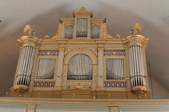 I Forsa kyrkas orgelfasad från 1850 finns inga ljudande pipor. Stora ringformade, skymmande, drygt 100 år yngre takarmaturer hindrar en mindre nackbrytande fotovinkel.