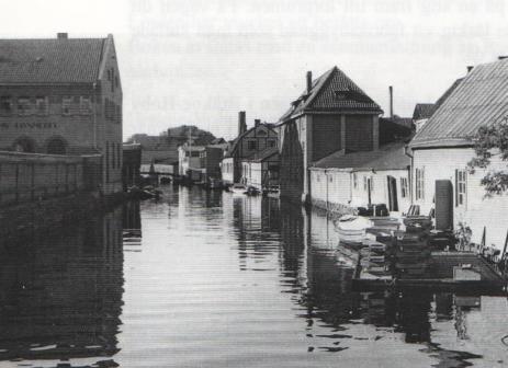 Huset med valmat tak till höger om ån var Ekens fabrikslokaler i Karlshamn. (Fotograf okänd)